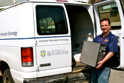 man unloading computer equipment from van